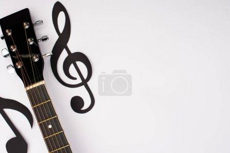 Photo pour Top view of paper cut music notes and acoustic guitar on white background - image libre de droit