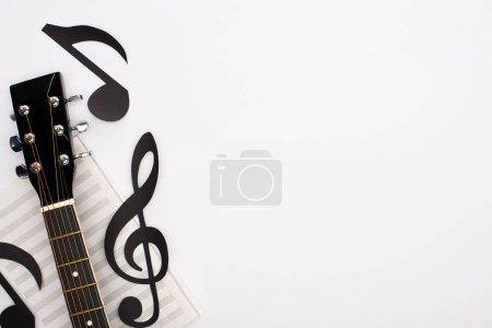 Photo pour Vue du dessus des notes coupées en papier, du livre de musique et de la guitare acoustique sur fond blanc - image libre de droit