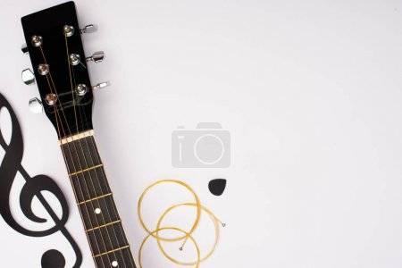 Photo for Top view of acoustic guitar and paper cut music note on white background - Royalty Free Image