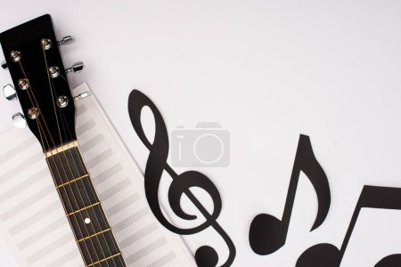 Photo pour Top view of paper cut notes near music book and acoustic guitar on white background - image libre de droit