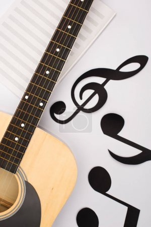 Photo pour Top view of paper cut notes near music book with acoustic guitar on white background - image libre de droit