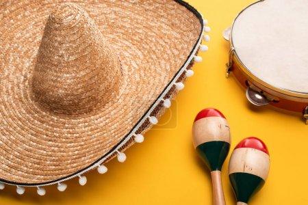 Photo pour Maracas colorés en bois près de sombrero et tambourin sur fond jaune - image libre de droit