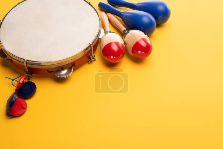Photo pour Wooden colorful and blue maracas with tambourine and castanets on yellow background - image libre de droit