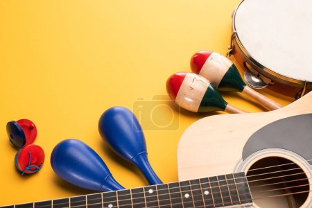 Photo for Wooden colorful and blue maracas with tambourine, castanets and acoustic guitar on yellow background - Royalty Free Image