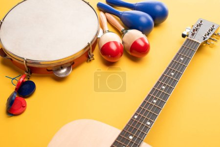 Photo pour Wooden colorful and blue maracas, tambourine, castanets and acoustic guitar on yellow background - image libre de droit