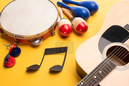 Photo for Musical instruments and paper cut music note on yellow background - Royalty Free Image