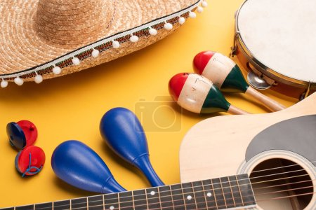 Photo for Musical instruments and mexican sombrero on yellow background - Royalty Free Image