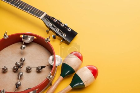 Photo for Tambourine near colorful wooden maracas and acoustic guitar on yellow background - Royalty Free Image