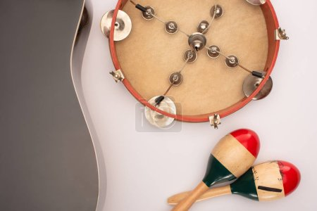 Photo for Top view of acoustic guitar near wooden maracas and tambourine on white - Royalty Free Image