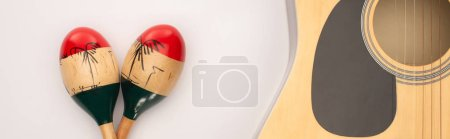 Photo for Top view of acoustic guitar near wooden maracas on white, panoramic shot - Royalty Free Image