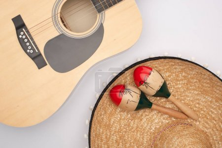 Top view of acoustic guitar with wooden maracas on sombrero on white background