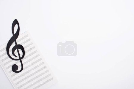 Photo for Top view of black paper cut note with music book on white background - Royalty Free Image