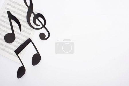 Photo pour Top view of paper cut black notes on music book on white background - image libre de droit