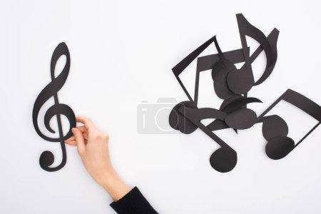 Photo pour Partial view of female hand with black paper cut music notes on white background - image libre de droit