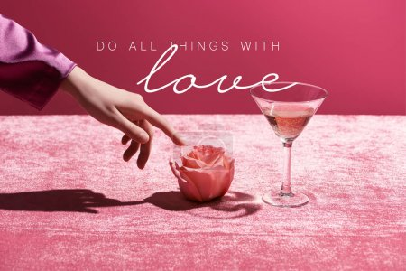 Photo pour Cropped view of woman touching rose near glass with drink on velour cloth isolated on pink, do all thing with love illustration - image libre de droit
