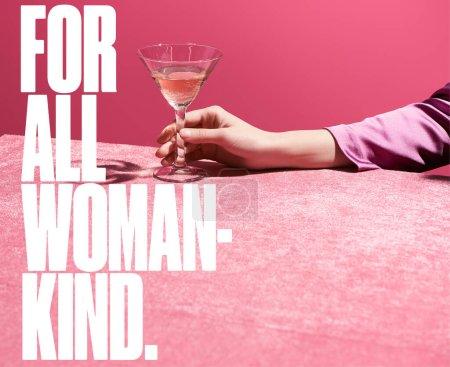 Photo pour Vue recadrée d'une femme tenant un verre de vin rose sur un tissu de velours isolé sur du rose, pour toutes les femmes illustration aimable - image libre de droit
