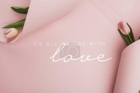 Photo pour Vue du haut des tulipes de printemps enveloppées dans des tourbillons de papier sur fond rose, faites tout avec l'illustration d'amour - image libre de droit