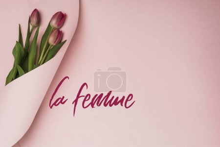 Photo for Top view of purple tulips wrapped in paper on pink background, la femme illustration - Royalty Free Image