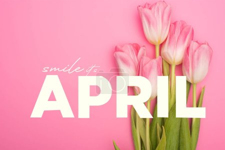 Photo pour Top view of tulips on pink background, smile, it is april illustration - image libre de droit