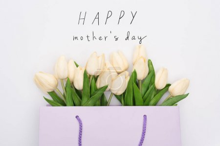 Photo pour Top view of tulips in violet shopping bag isolated on white, happy mothers day illustration - image libre de droit
