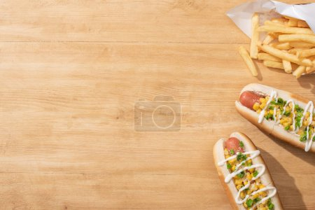 top view of delicious hot dogs with corn, green onion and mayonnaise near french fries on wooden table