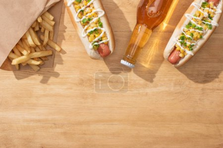top view of delicious hot dogs with corn, green onion and mayonnaise near french fries and beer on wooden table