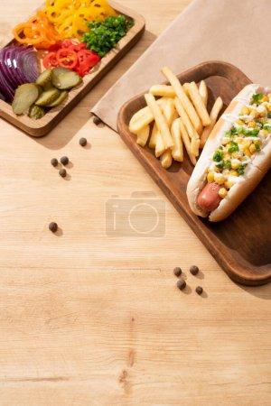 delicioso perrito caliente cerca de bordo con verduras en rodajas y papas fritas en la mesa de madera