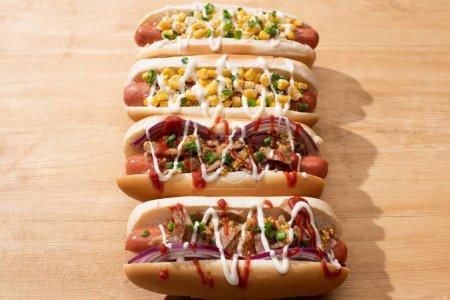 Photo pour Délicieux hot dogs avec oignon rouge, bacon et maïs sur table en bois. - image libre de droit
