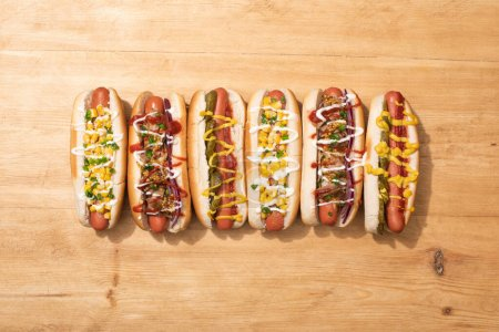 Photo for Top view of various delicious hot dogs with vegetables and sauces on wooden table - Royalty Free Image