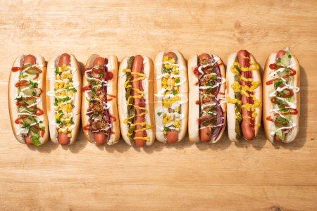 Photo pour Vue de dessus de divers délicieux hot-dogs aux légumes et sauces sur table en bois - image libre de droit