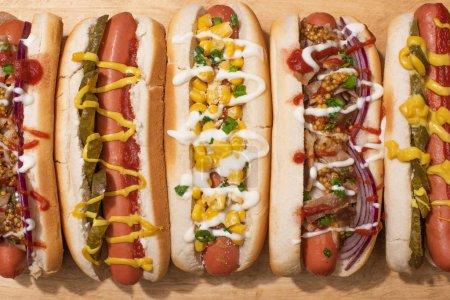 Photo pour Vue de haut de divers hot dogs délicieux avec légumes et sauces sur table en bois - image libre de droit