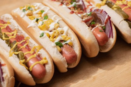 Photo for Various delicious hot dogs with vegetables and sauces on wooden table - Royalty Free Image