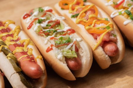 Photo for Fresh various delicious hot dogs with vegetables and sauces on wooden table - Royalty Free Image