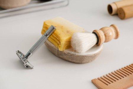 Photo pour Vue rapprochée du plat avec savon, brosse à raser et rasoir près du peigne sur gris, concept zéro déchet - image libre de droit