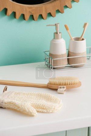 Photo pour Produits d'hygiène sur étagère près de brosse de massage et gant de bain dans la salle de bain, concept zéro déchet - image libre de droit
