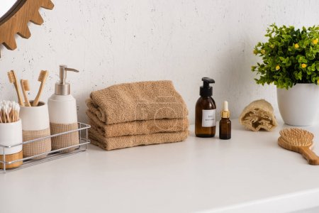 Photo for Shelf with hygiene objects near towels, beauty products and flowerpot in bathroom, zero waste concept - Royalty Free Image