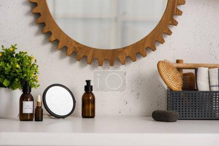 Photo pour Boîte avec peigne, brosse à cheveux et serviettes près des produits cosmétiques et pot de fleurs dans la salle de bain, concept zéro déchet - image libre de droit