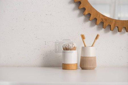 Photo pour Porte-brosses à dents avec brosses à dents et bâtons d'oreille près du miroir rond sur le mur dans la salle de bain, concept zéro déchet - image libre de droit
