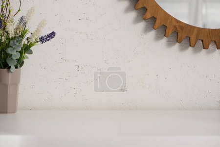 Photo for Flowerpot with flowers and round mirror on wall in bathroom, zero waste concept - Royalty Free Image