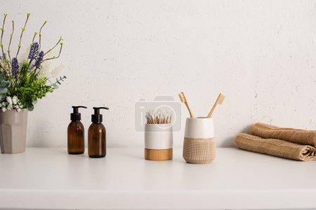Photo pour Pot de fleurs, crème pour le corps eco, porte-brosses à dents avec objets d'hygiène et serviettes dans la salle de bain, concept zéro déchet - image libre de droit