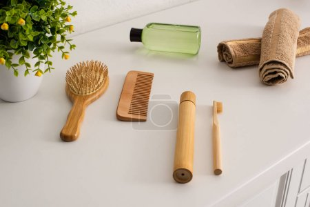 Photo for Flowerpot, bottle of cosmetic oil, towels and eco friendly hygiene objects in bathroom, zero waste concept - Royalty Free Image