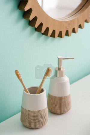 Photo pour Porte-brosse à dents avec brosses à dents et savon liquide près miroir rond sur le mur dans la salle de bain, concept zéro déchet - image libre de droit