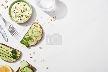 Photo for Top view of fresh cucumber toasts near lemon, water, cutlery and yogurt on white background - Royalty Free Image