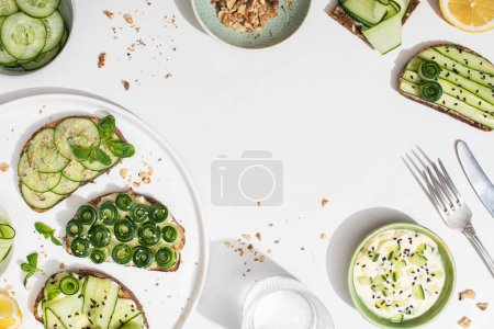 Photo for Top view of fresh cucumber toasts on plate near lemon, water, cutlery and yogurt on white background - Royalty Free Image
