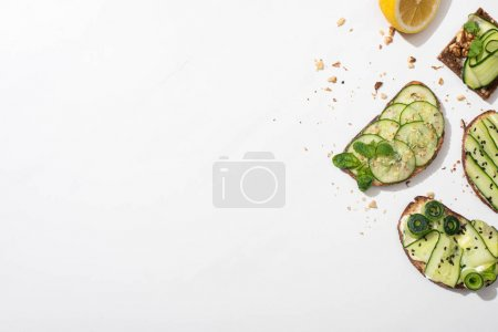 Photo for Top view of fresh cucumber toasts with seeds, mint and basil leaves and lemon on white background - Royalty Free Image