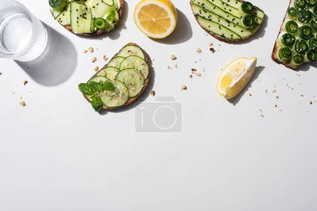Photo pour Vue de dessus des toasts au concombre frais avec graines, menthe et feuilles de basilic, citron près de l'eau sur fond blanc - image libre de droit