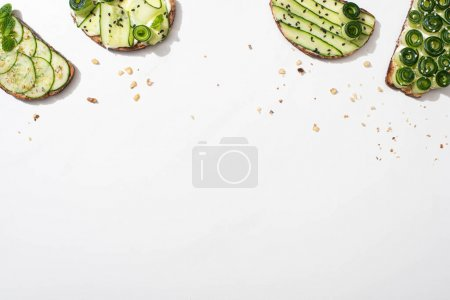 Photo for Top view of fresh cucumber toasts with seeds, mint and basil leaves on white background - Royalty Free Image