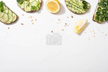 Photo pour Vue de dessus des toasts au concombre frais avec des graines, des feuilles de menthe et de basilic et du citron sur fond blanc - image libre de droit