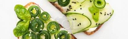 Photo for Top view of fresh cucumber toasts with seeds and basil leaves isolated on white, panoramic shot - Royalty Free Image