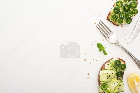 Photo for Top view of fresh cucumber toasts with seeds, basil leaves and cutlery on white background - Royalty Free Image